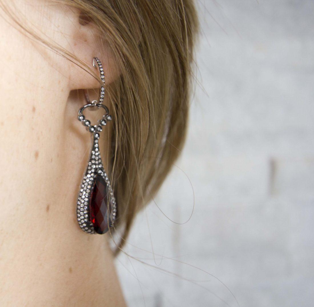 Woman Wearing a Red Teardrop-Shaped Gemstone Earring